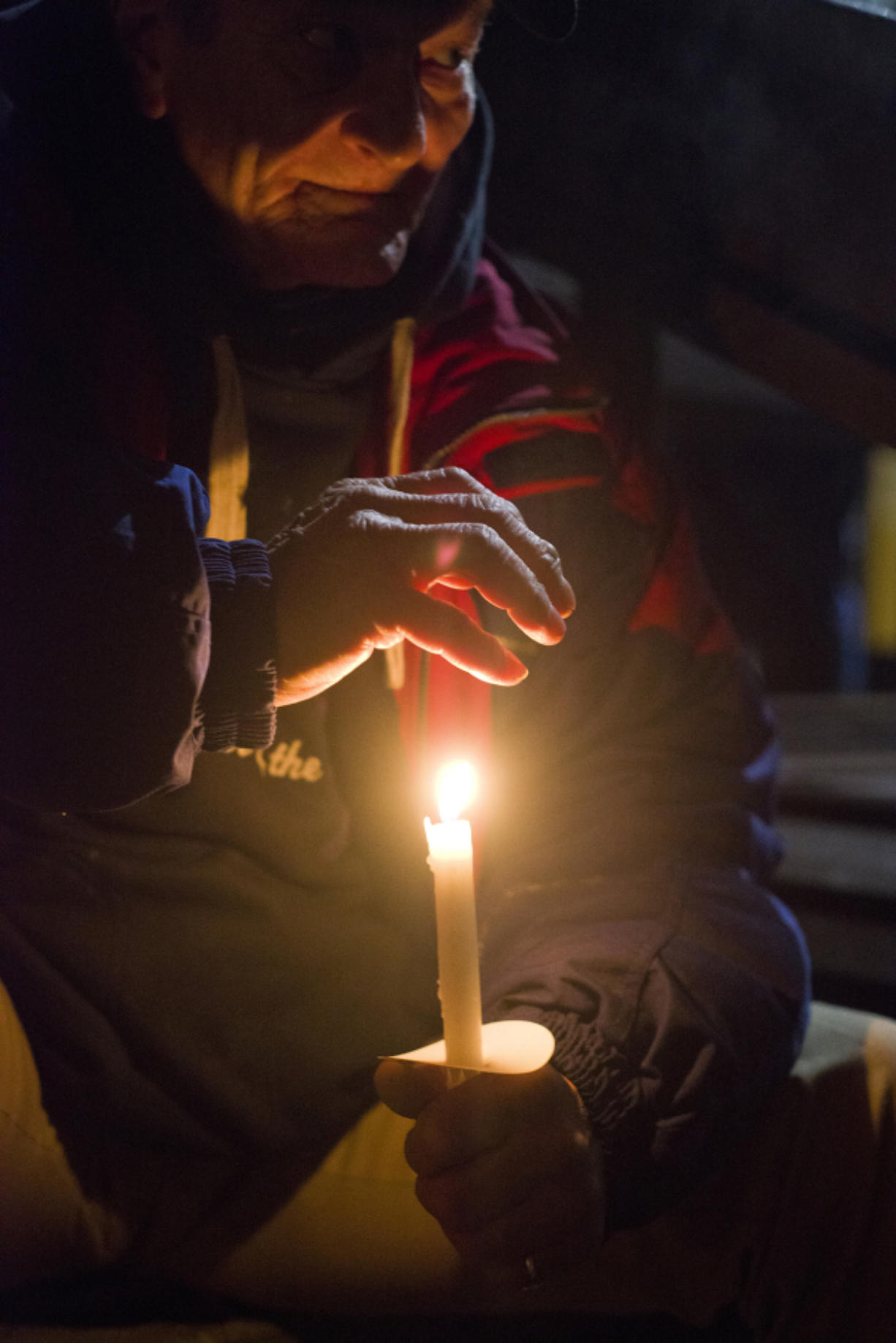 Robert Langford warms his hand with a candle during a homeless memorial service Wednesday night at St. Paul Lutheran Church in Vancouver.