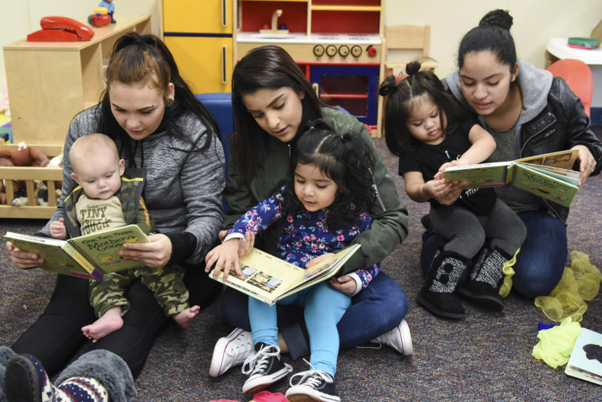 From left to right, Stephanie Watson and her son, Zaine Post; Vanessa Toscano and her daughter, Jaylah Castro; and Fanny Lopez and her daughter, Alexandra Lopez, read together Dec. 13 during story time in the GRADS program at Evergreen High School. A recent state study found that for every dollar invested in the program, students benefit by three times as much. (Ariane Kunze/The Columbian)