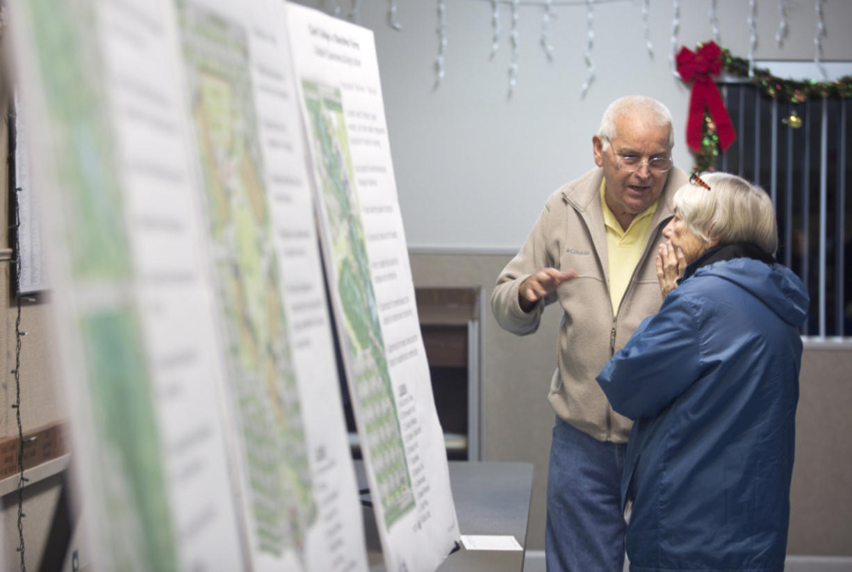 Gerald Jones and his neighbor Barbara Staudacher look at plans for a new Clark County campus in east Ridgefield. The college presented the final master plan for the new campus Monday at the Ridgefield Community Center. (Natalie Behring for the Columbian)