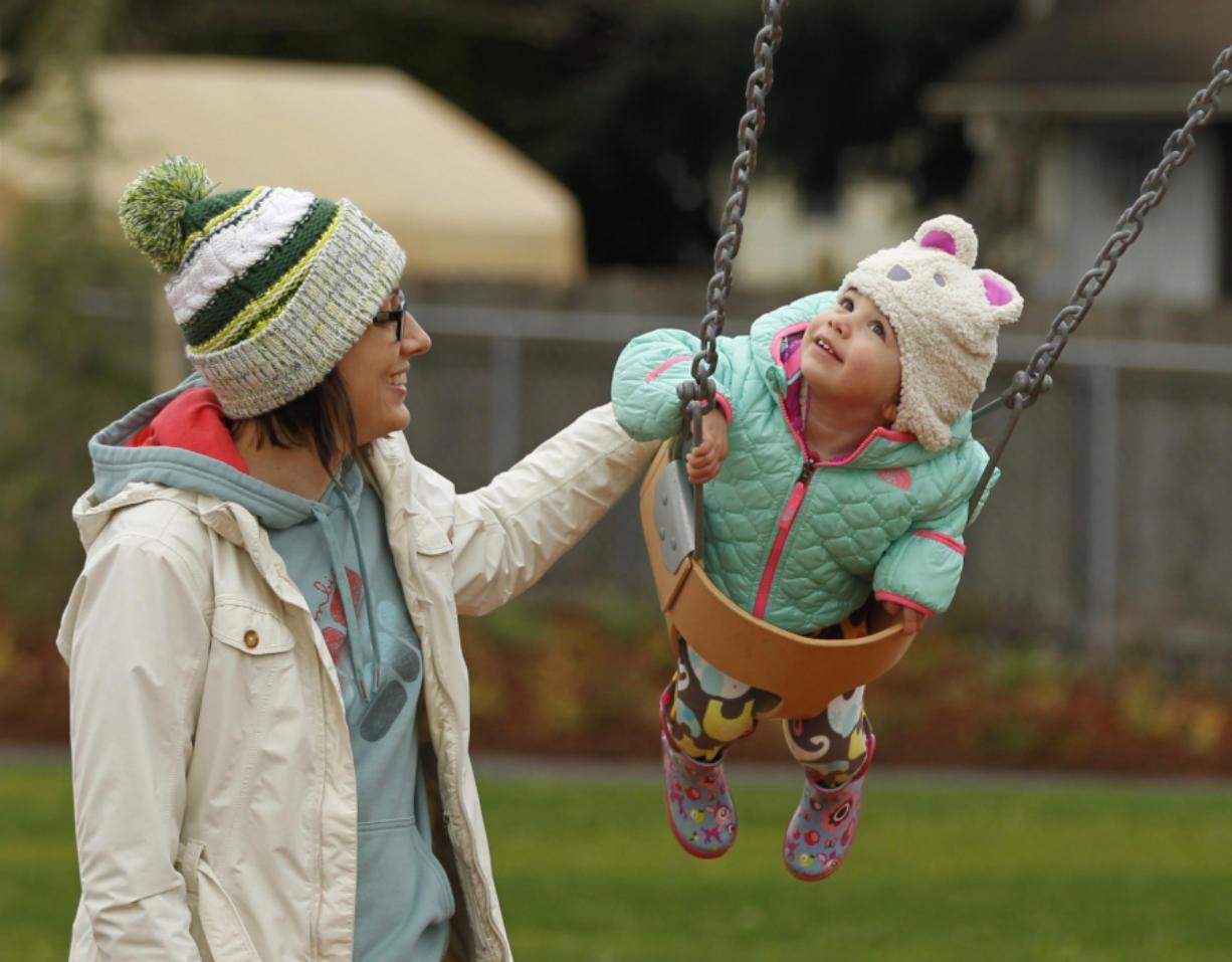 Sarah Bunn and her daughter Parker, 2, enjoy the swings Saturday as the Felida Neighborhood Association officially opens Sorenson Park.