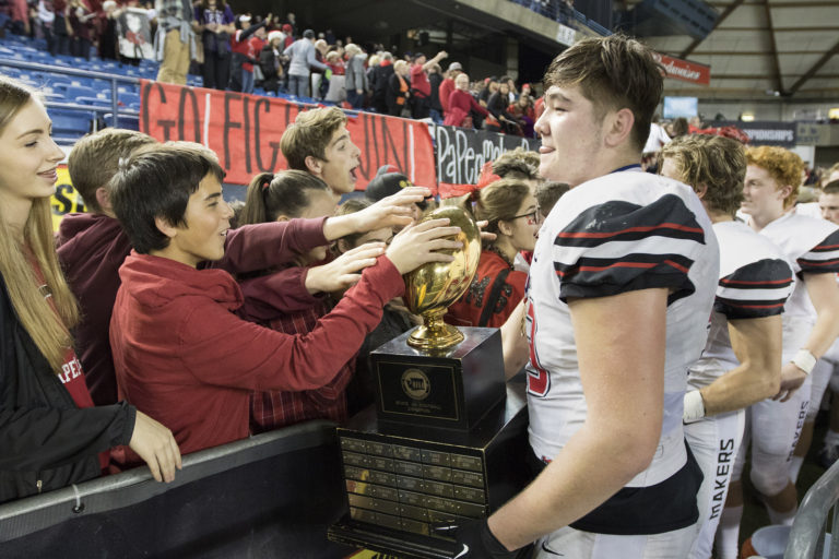 Camas' Marshall McIvor, right, brings the trophy to the Camas fans after Camas defeated  Richland in the 4A State Football Championship game Saturday, Dec. 3, 2016,  in Tacoma, Wash.