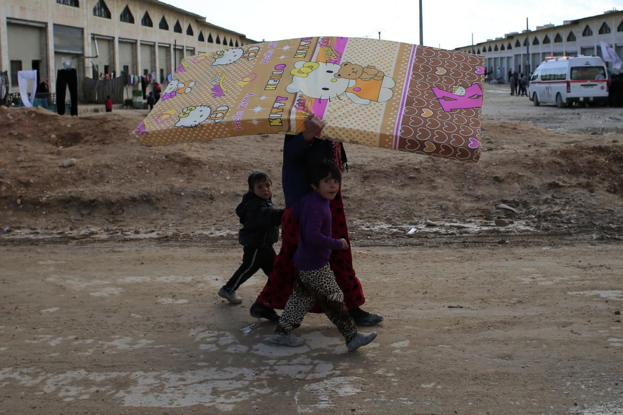 A Syrian woman displaced with her family from eastern Aleppo walks with her children as she carries a mattress in the village of Jibreen south of Aleppo, Syria, Saturday, Dec. 3, 2016. Aid agencies say that more than 30,000 people have fled rebel-held eastern neighborhoods of Aleppo that have been under tight siege since July. Over the past two weeks, government forces launched an offensive in which they regained control of nearly half areas that had been held by insurgents in their deepest push since the city became contested in July 2012.(AP Photo/Hassan Ammar)