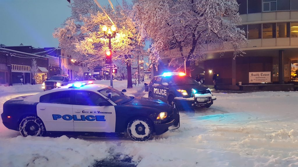 Vancouver police vehicles block the intersection at Sixth and Washington in downtown for a power line brought down by a snow-covered branch.