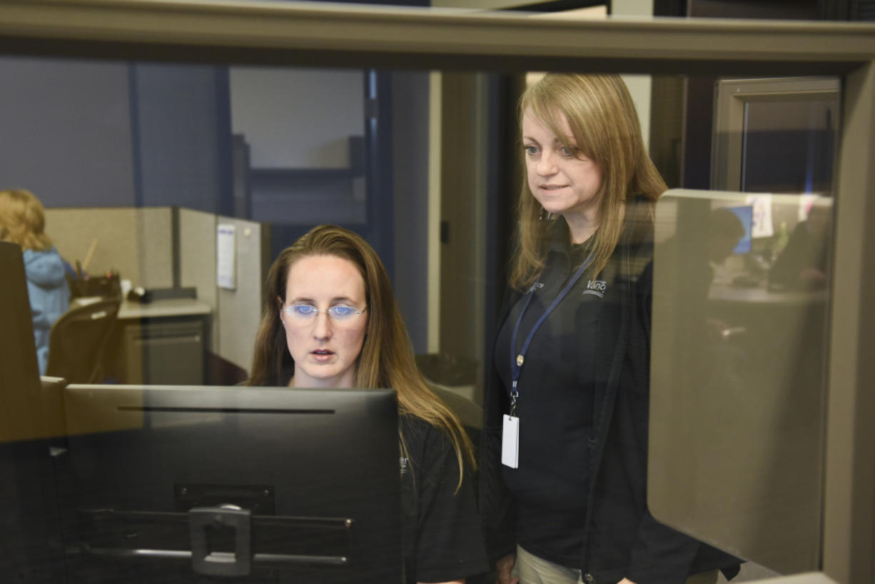 Police records specialist Sara Cox works with records supervisor Gail Truax at the Vancouver Police Department's West Precinct in the new records office last month.