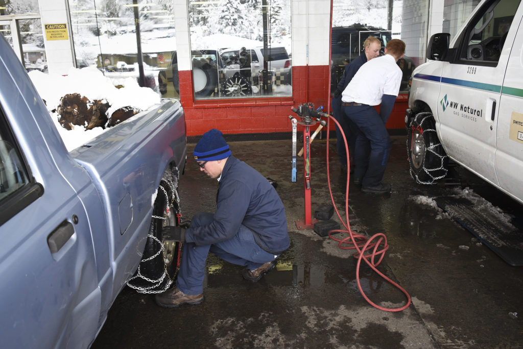 Les Schwab employees put chains on a vehicles at the Les Schwab in Hazel Dell in 2017.