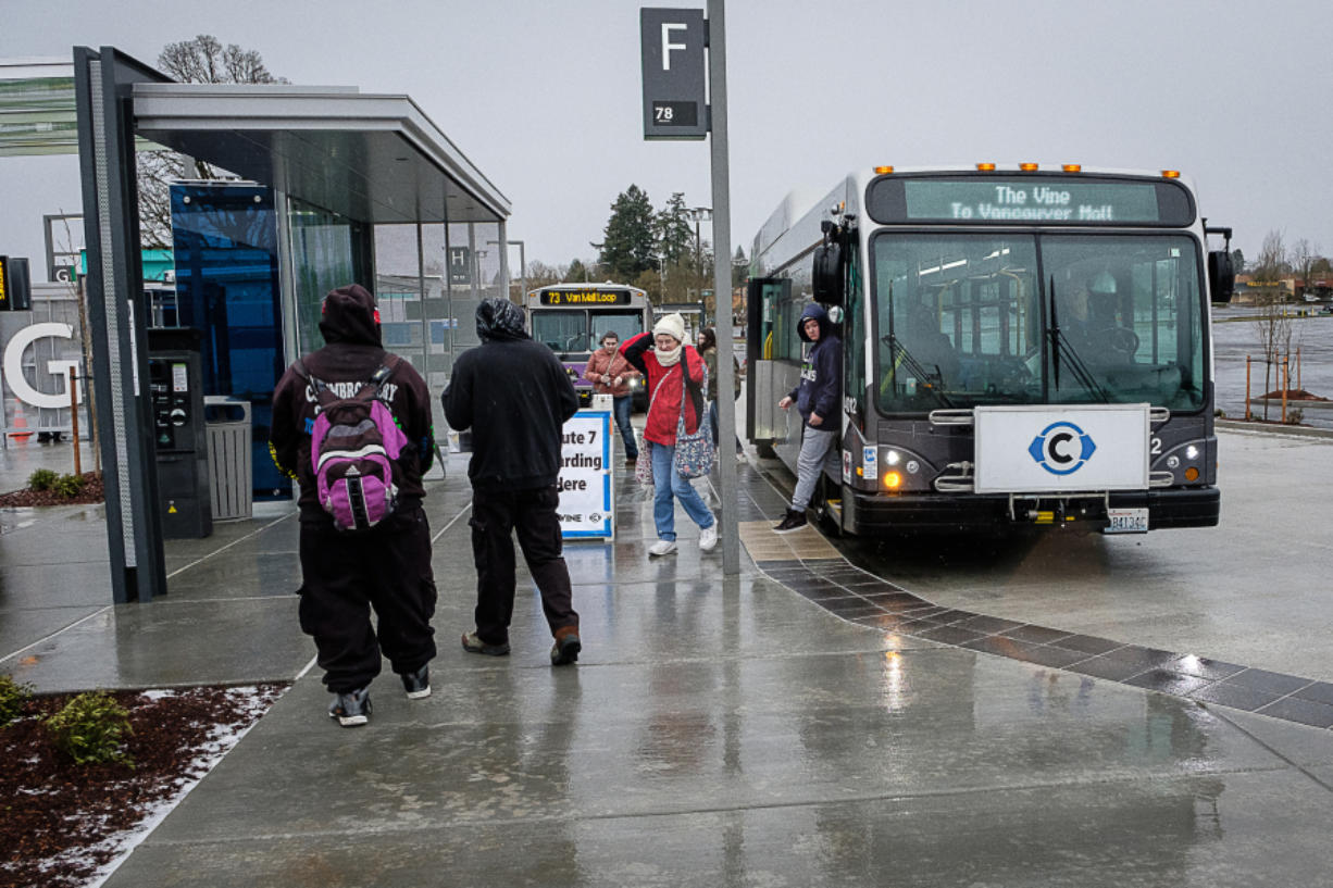 Passengers cope with cold, wet weather to catch The Vine from the Vancouver Mall Transit Center on Sunday. The service operated with regular buses and on a modified route on its opening day due to adverse weather conditions. (Joseph Glode for The Columbian)