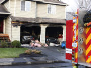 Firefighters respond to a structure fire Sunday morning in the Salmon Creek area that damaged an attached garage and the vehicles inside of it.