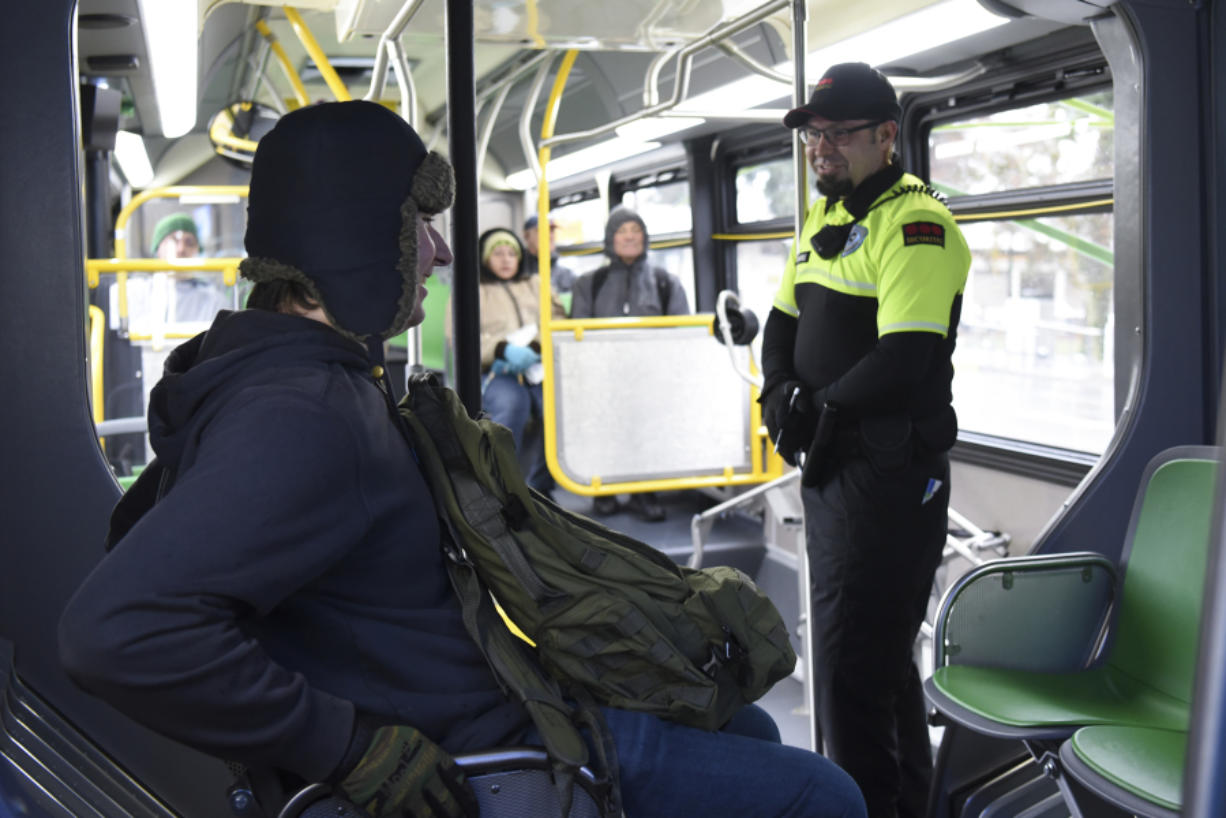 Ethan Greagor, left, talks with Max Wajda, a C-Tran fare compliance officer, while riding The Vine. The compliance officers will check for tickets, which are bought in advance, not from the driver. (Ariane Kunze/The Columbian)