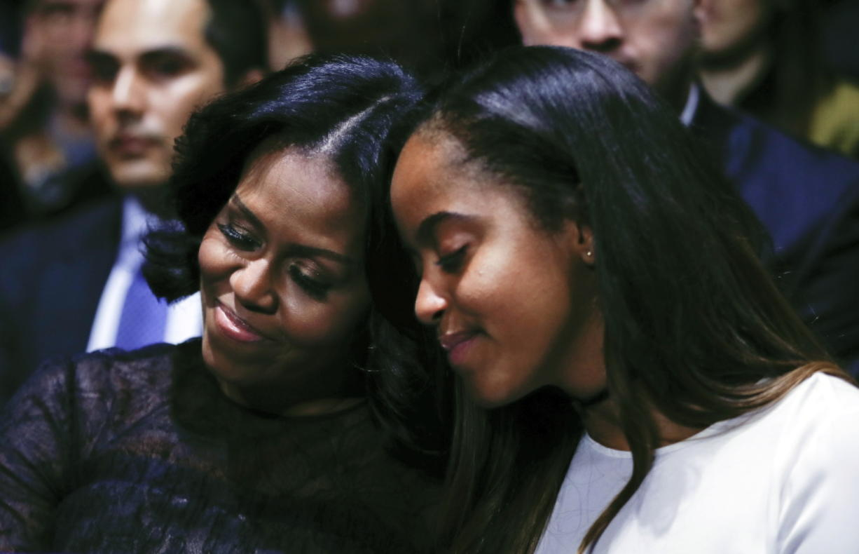 First lady Michelle Obama and daughter Malia lean into one another as they listen to President Barack Obama speak during his farewell address at McCormick Place in Chicago, Tuesday, Jan. 10, 2017.