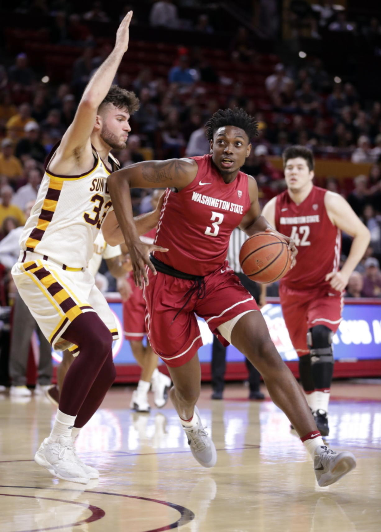 Washington State forward Robert Franks, an Evergreen High School grad, drives past Arizona State forward Ramon Vila (33) during the first half Sunday in Tempe, Ariz. Franks scored six points and made three of four field goals.