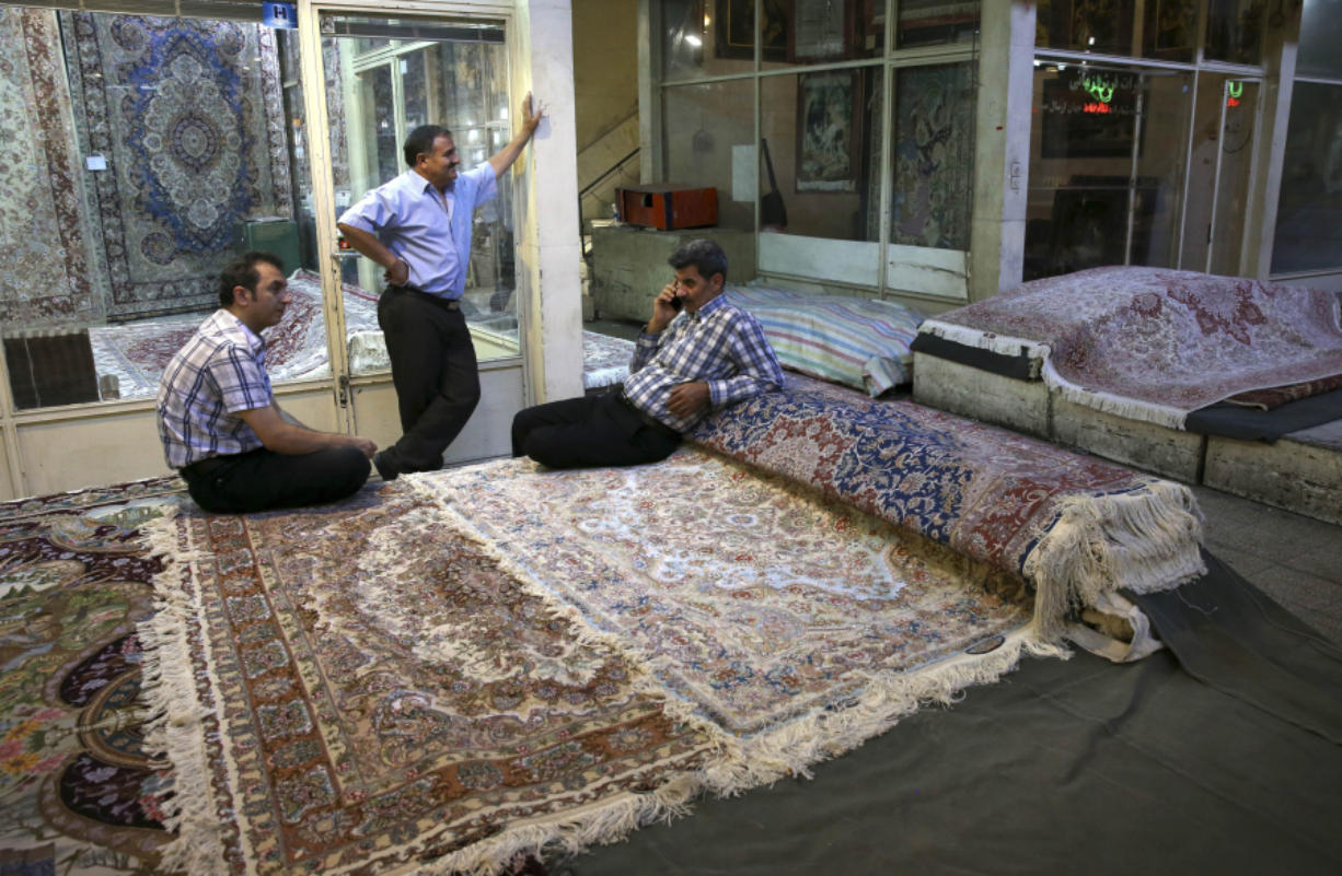 Iranian merchants wait for customers at a carpet market in 2015 in Tehran's old, main bazaar, in Iran. Bazaars such as this, along with mosques, museums and other sites, are on itineraries for sightseeing trips to Iran offered by tour companies.
