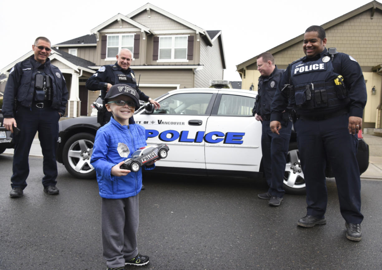 Nick Zadak, 4, smiles back at his mom before getting into a police car for a ride-along with Vancouver Neighborhood Police Officers, Tyler Chavers, from left, James Burgara, Erik Jennings and Mac Shipp at Zadak's home in Vancouver on Jan. 25. Nick died Thursday after battling hepatoblastoma, a pediatric liver cancer. (Ariane Kunze/The Columbian)