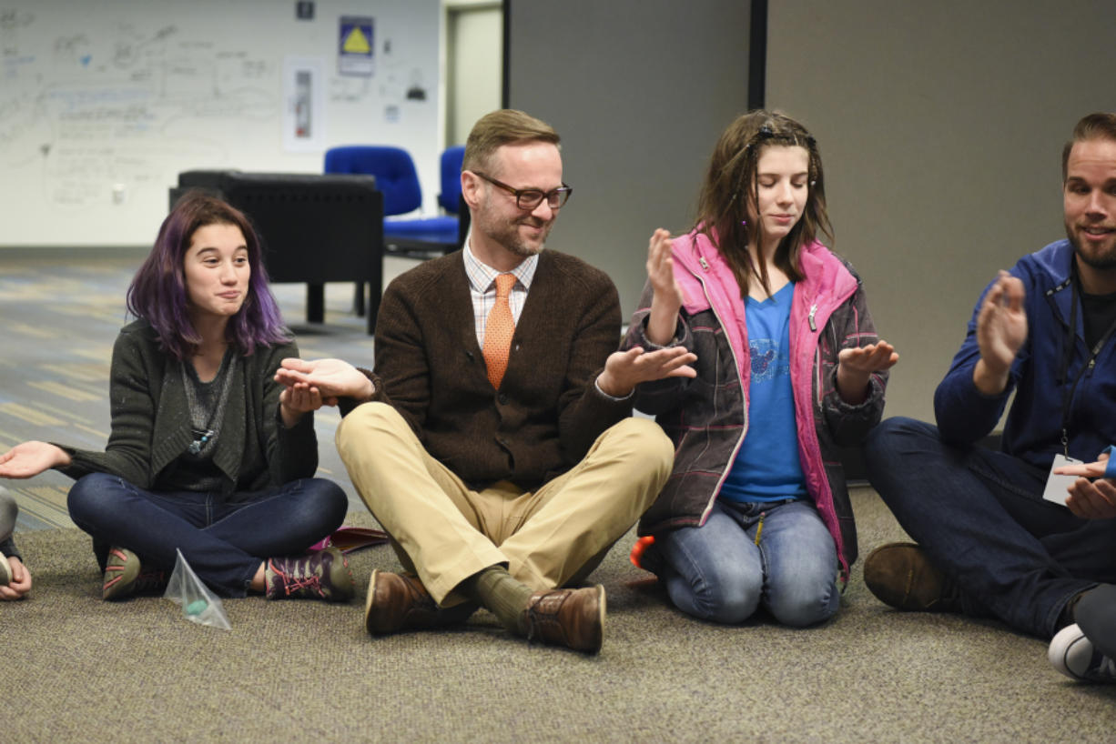 """Principal Aaron Smith, center, plays the game """"Down by the Banks"""" with seventh-graders May Williamson-Shilling, left, and Regan VanCleave, before class at the Camas Project-Based Learning Middle School."""