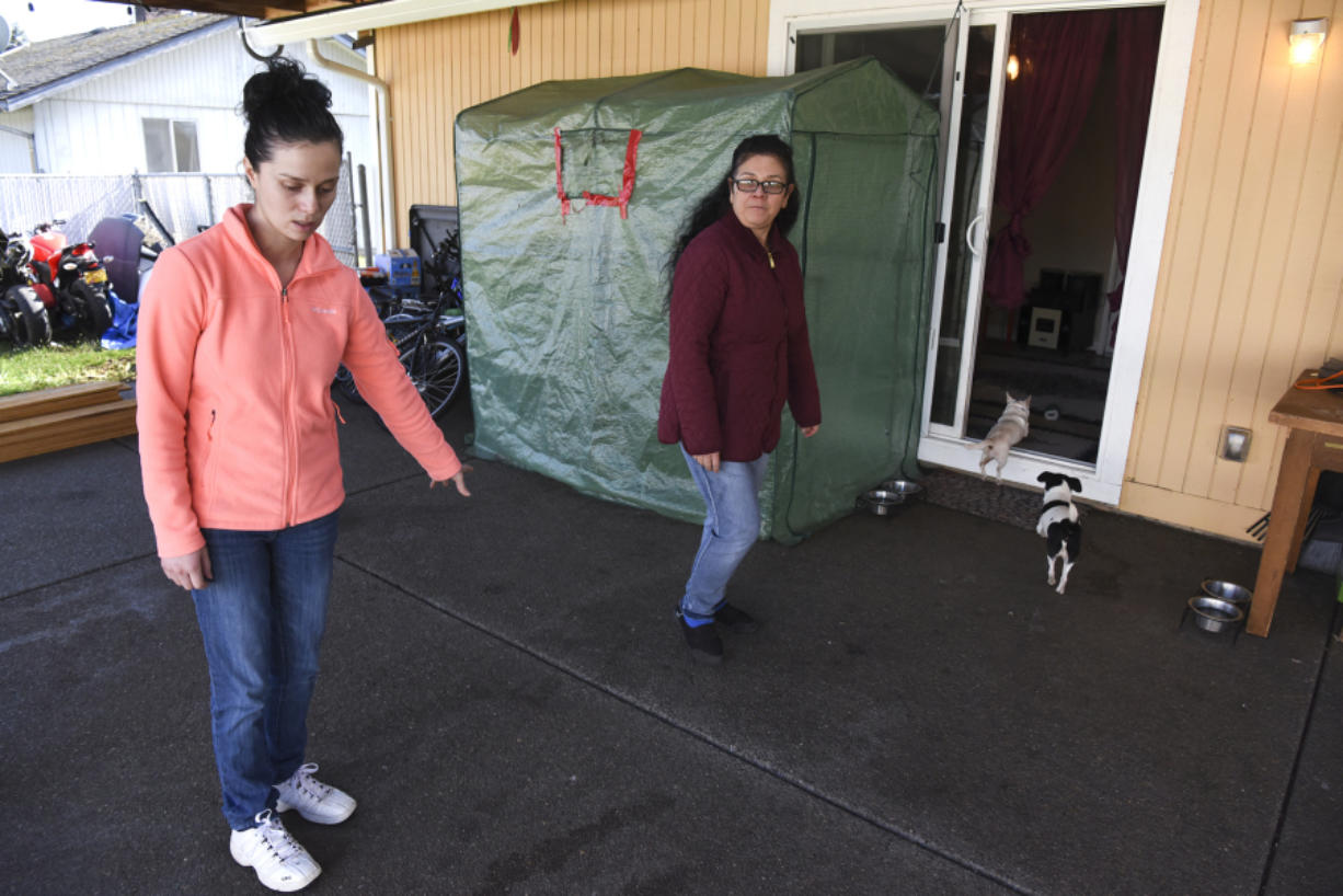 Ana Govea, left, points to the spot where Jane, a pit bull, attacked and killed Princess, her Chihuahua. Govea's mother, Maria Gonzalez, center, was home with several small children when Jane broke through the backyard gate.