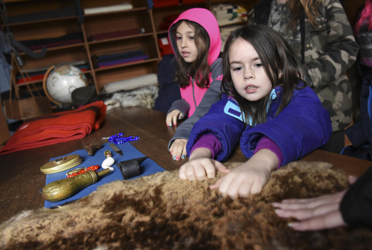 Lillyannah Cook-Forsht, a Washington Connections Academy student, right, feels an animal pelt, while Iris MacMichael waits for a turn.