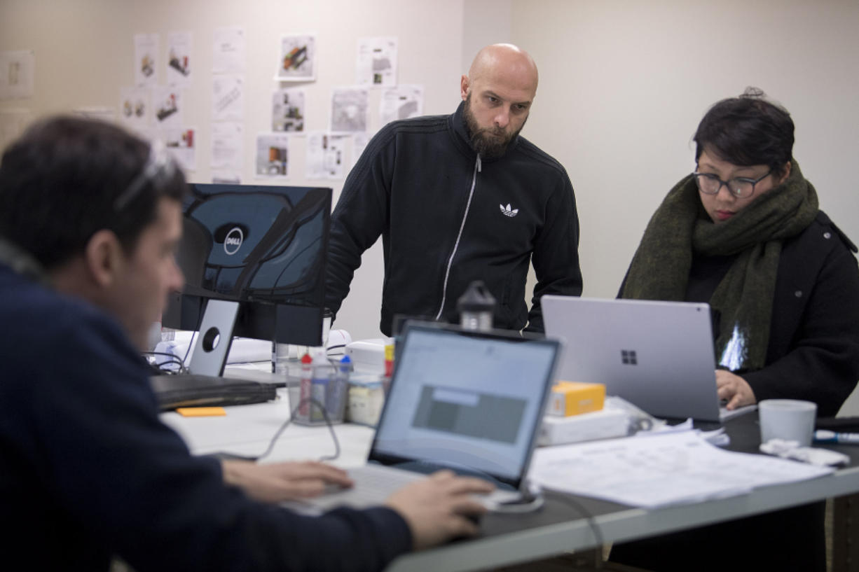 Blokable will make modular housing, in pieces sized like shipping containers, en masse beginning in April. Luke Olszewski, center, and My Tam Nguyen work in the Vancouver office on a recent Wednesday.
