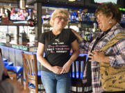 Nancy Koon, right, consoles her sister, Best Friends Dog Grooming owner Sue Picchioni, during a fundraiser Sunday morning at Hooligan's Sports Bar & Grill in Vancouver. Best Friends lost its shop in the Sifton Market fire in January.