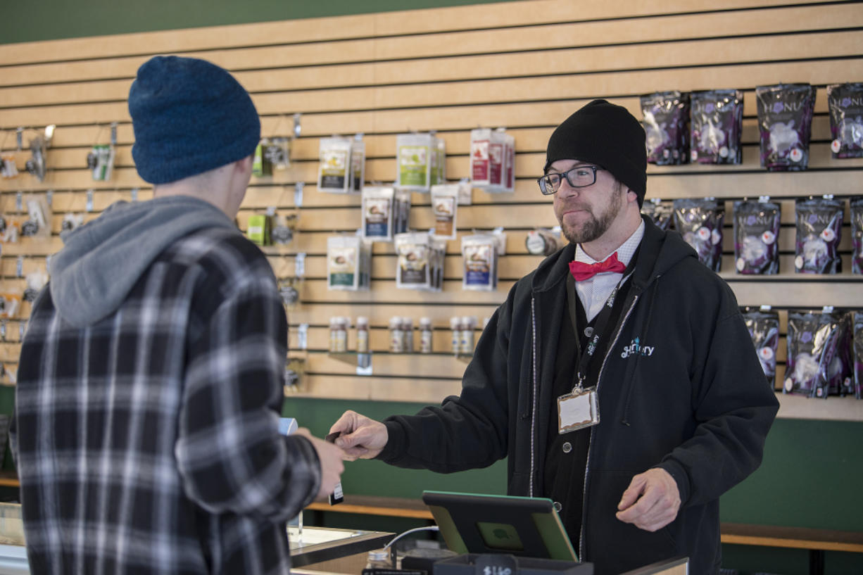 Budtender Jeff Sellers assists a customer with a purchase at The Herbery. Jim Mullen, the store's owner, said it hopes to win customers' loyalty with service as the price of marijuana flowers tumbles.