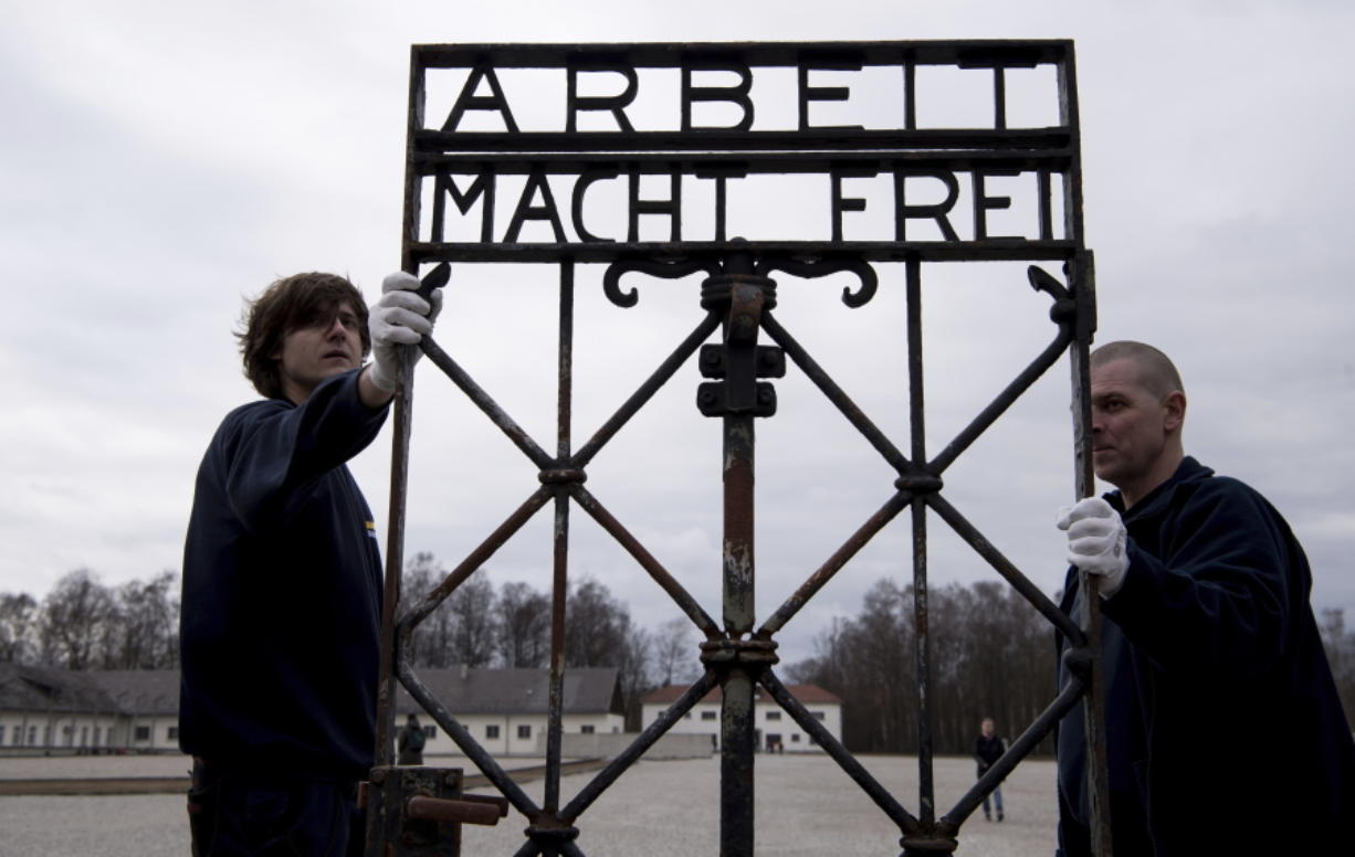 """Employees of a transport company carry the gate with the writing """"Arbeit macht frei"""" (Work Sets you Free) at the memorial of the former  Nazi concentration camp in Dachau, Germany, on Wednesday. The gate was stolen in 2014 and reappeared in November near the city of Bergen in Norway."""