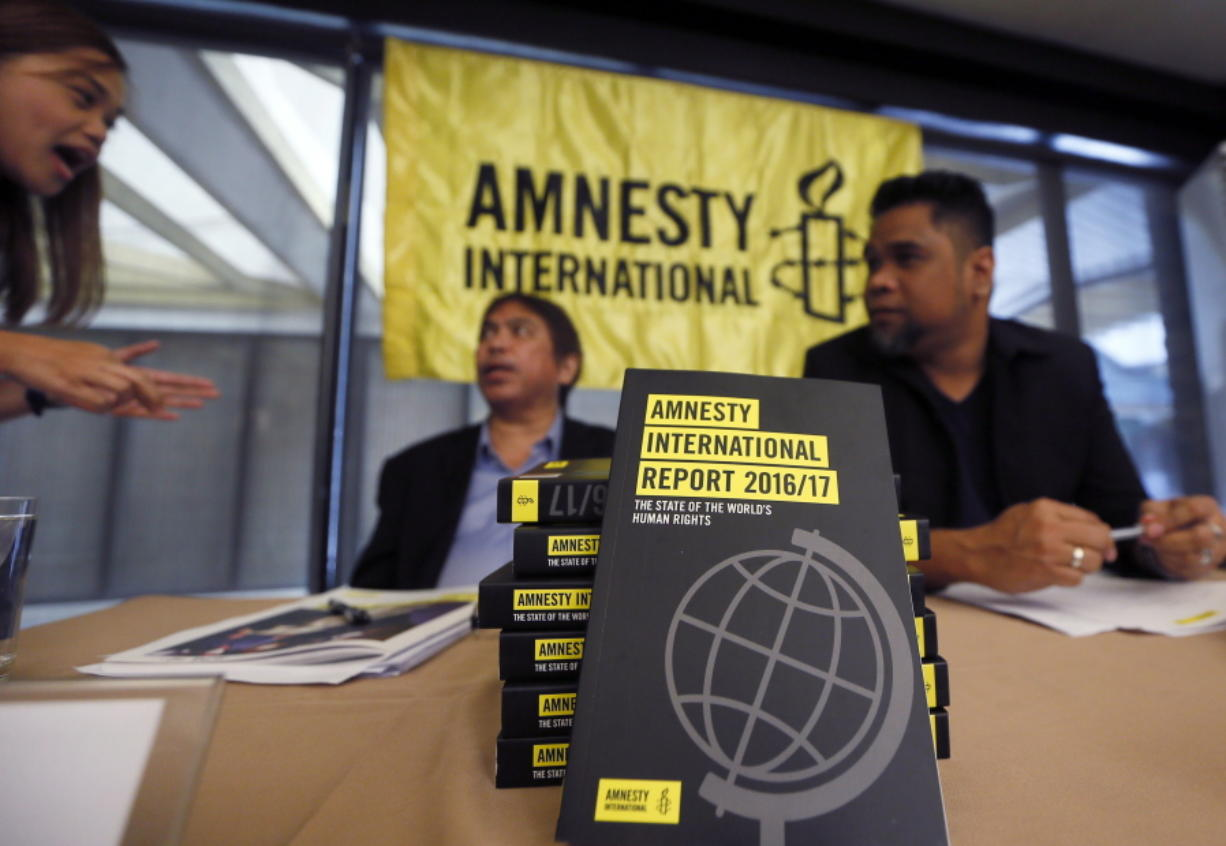 """A reporter, left, talks to Amnesty International, Philippines' Jose Noel Olano and Wilnor Papa, right, following the release of the 2016-17 Amnesty International report which they released at a news conference Wednesday in suburban Quezon city northeast of Manila, Philippines. Amnesty International says """"toxic"""" fear-mongering by anti-establishment politicians, among them President Donald Trump and the leaders of Turkey, Hungary and the Philippines, is contributing to a global pushback against human rights. (AP Photo/Bullit Marquez)"""