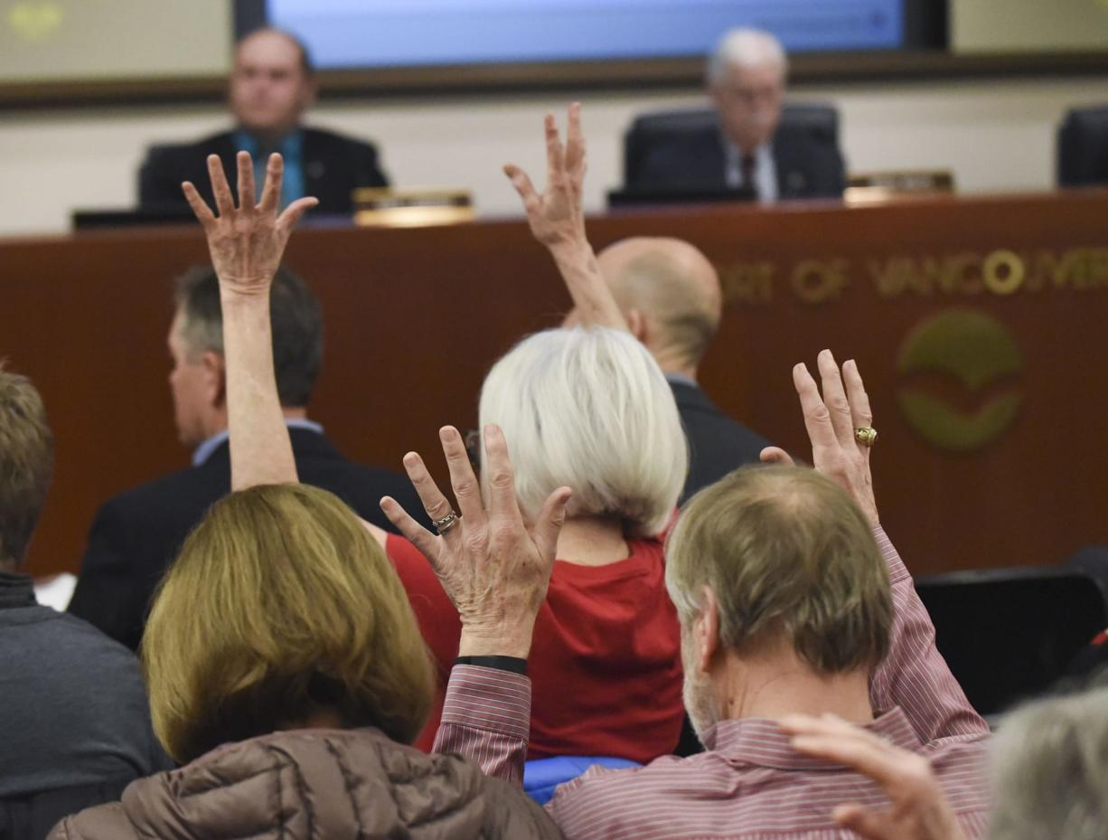 Community members in opposition to the proposed Vancouver oil terminal wave their fingers in support of commentary delivered at a board meeting of the Port of Vancouver Board of Commissioners on Tuesday.