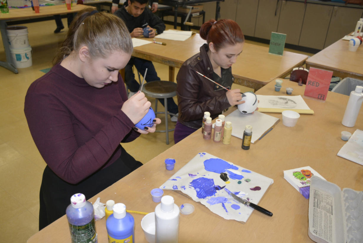 Washougal: Through a Washougal Schools Foundation mini grant, advanced arts students, such as Haleigh Metz, left, and Tianna Godin, made Zulu Coconuts by painting coconut shells that came in from Florida.