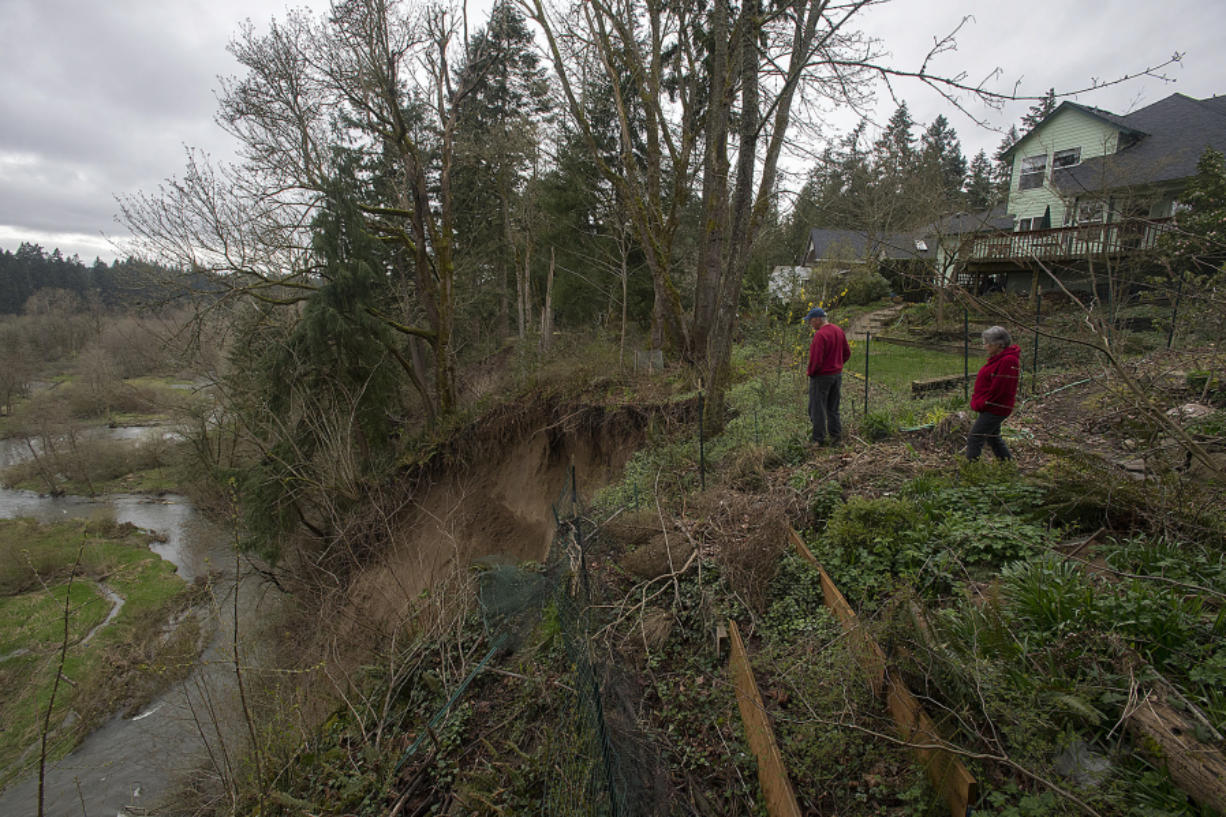 Clancy Kelly, left, and his neighbor Sarah Athay examine the aftermath of a landslide that occurred behind their Salmon Creek homes on Friday. For the past two years, a handful of slides have gnawed away at the slope behind their homes.