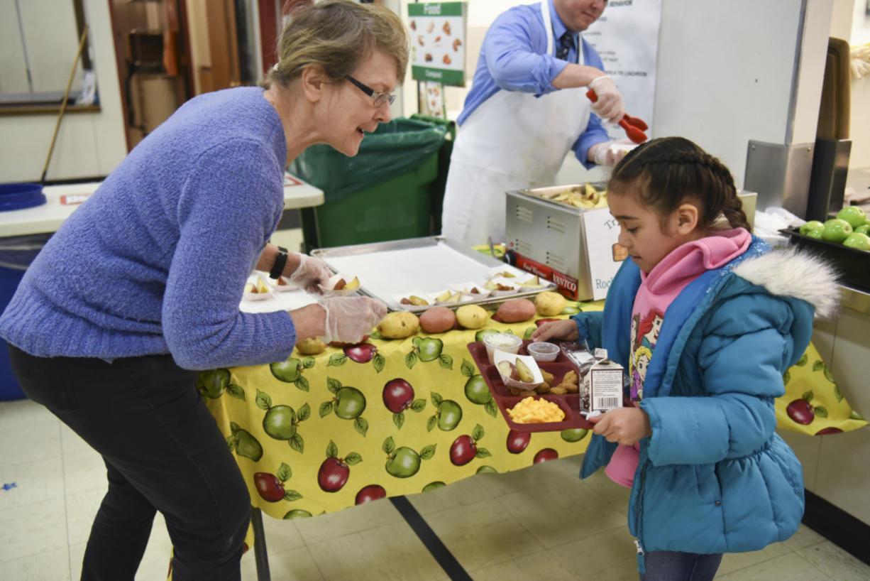 Marty Fields, nutrition educator for SNAP-Ed, serves roasted potato wedges to kindergartner Samantha Vargas.