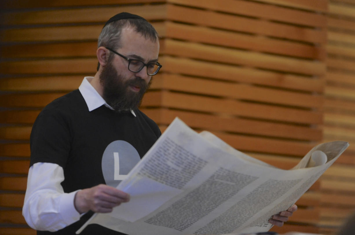Rabbi Shmulik Greenberg reads the Megillah, or the story of the Book of Esther, at the Purim holiday celebration. (Greg Wahl-Stephens for the Columbian)