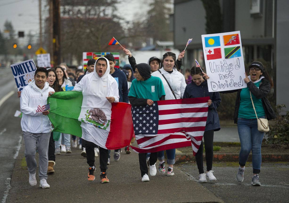 Vancouver students show their support for minority and immigrant students as they march along East Fourth Plain Boulevard on Monday afternoon. In an organized walkout, more than 100 students left class to protest the Trump administration's policies on immigration and to call on Vancouver Public Schools to issue a letter saying students are safe on campus.