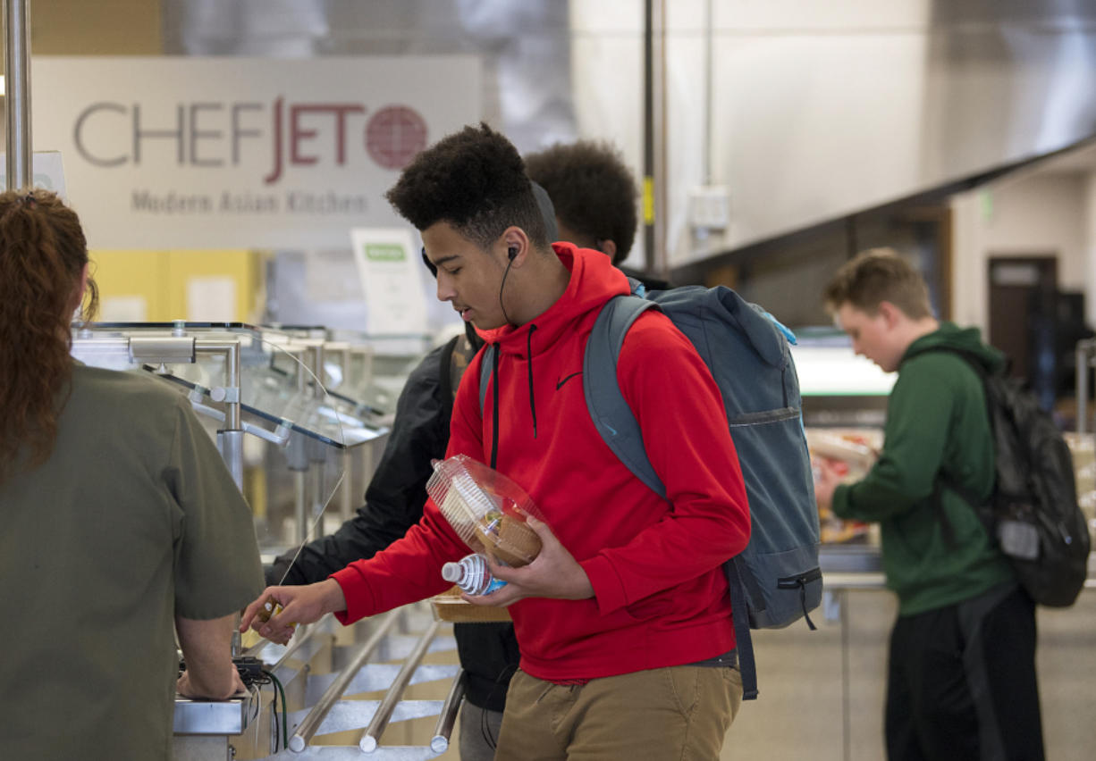 Freshman DeAndre Hampton, 15, listens to music as he picks up a meal after school at Evergreen High School on Tuesday afternoon. Students receive free meals after school to help fuel them for their evening activities.