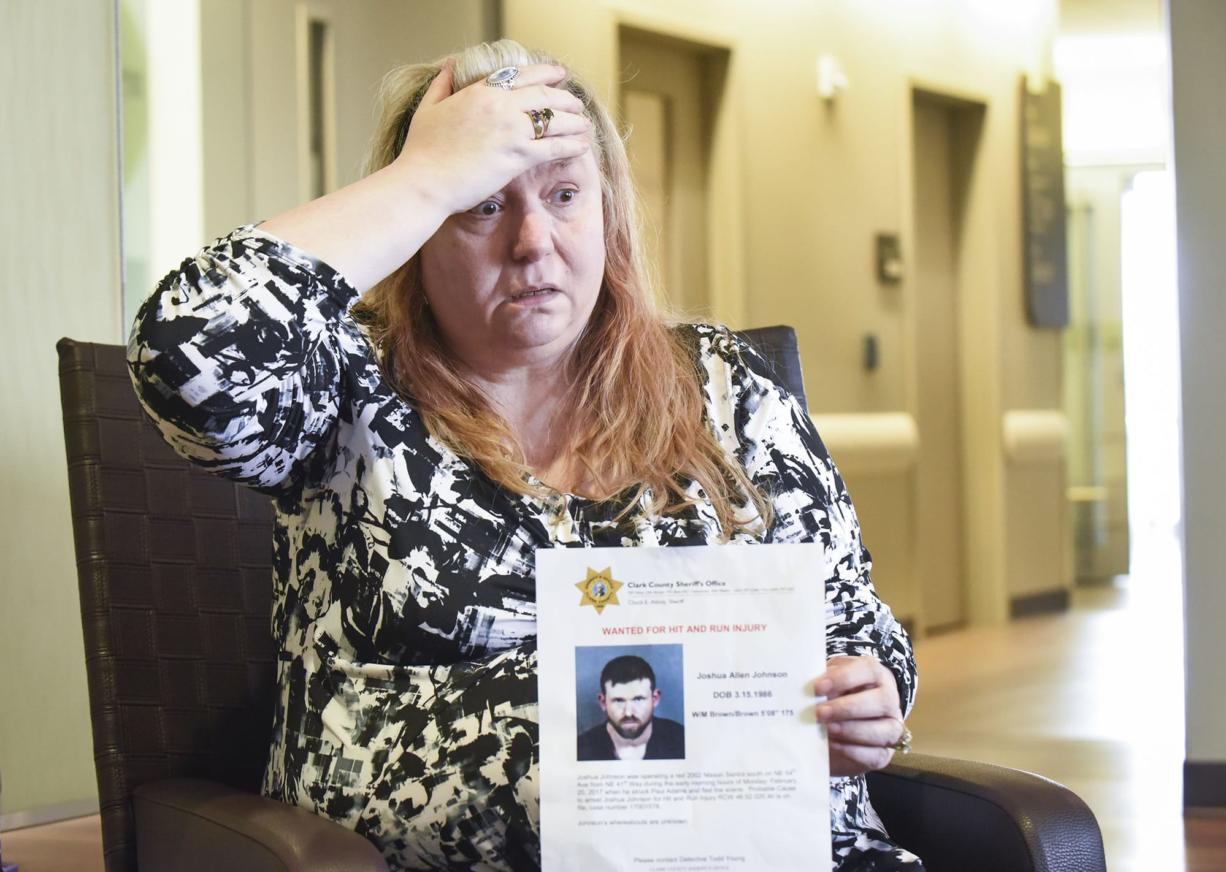 Nancy Peterson, mother of Paul Adams, who has been hospitalized since Feb. 20 when he was struck while walking along the road in Vancouver's Truman neighborhood, holds a wanted persons poster for Joshua Johnson, the driver suspected in the crash, Friday, March 24, 2017, at PeaceHealth Southwest Medical Center in Vancouver.