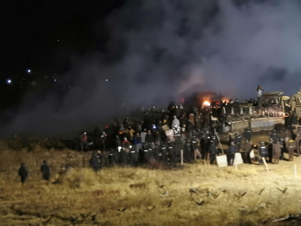 Law enforcement and protesters clash near the site of the Dakota Access pipeline near Cannon Ball, N.D., on Nov. 20. Prosecutors have withdrawn a subpoena for Steve Martinez, a pipeline opponent from Williston, N.D., who had been ordered to testify about the violent clash in November.