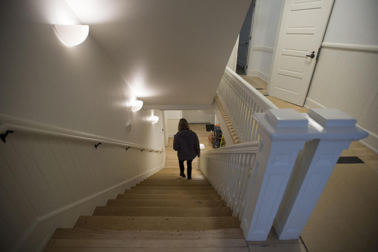 Public affairs officer Sue Ripp descends a staircase at Fort Vancouver National Historic Site after the Gifford Pinchot National Forest moved into the Vancouver Barracks building in January.