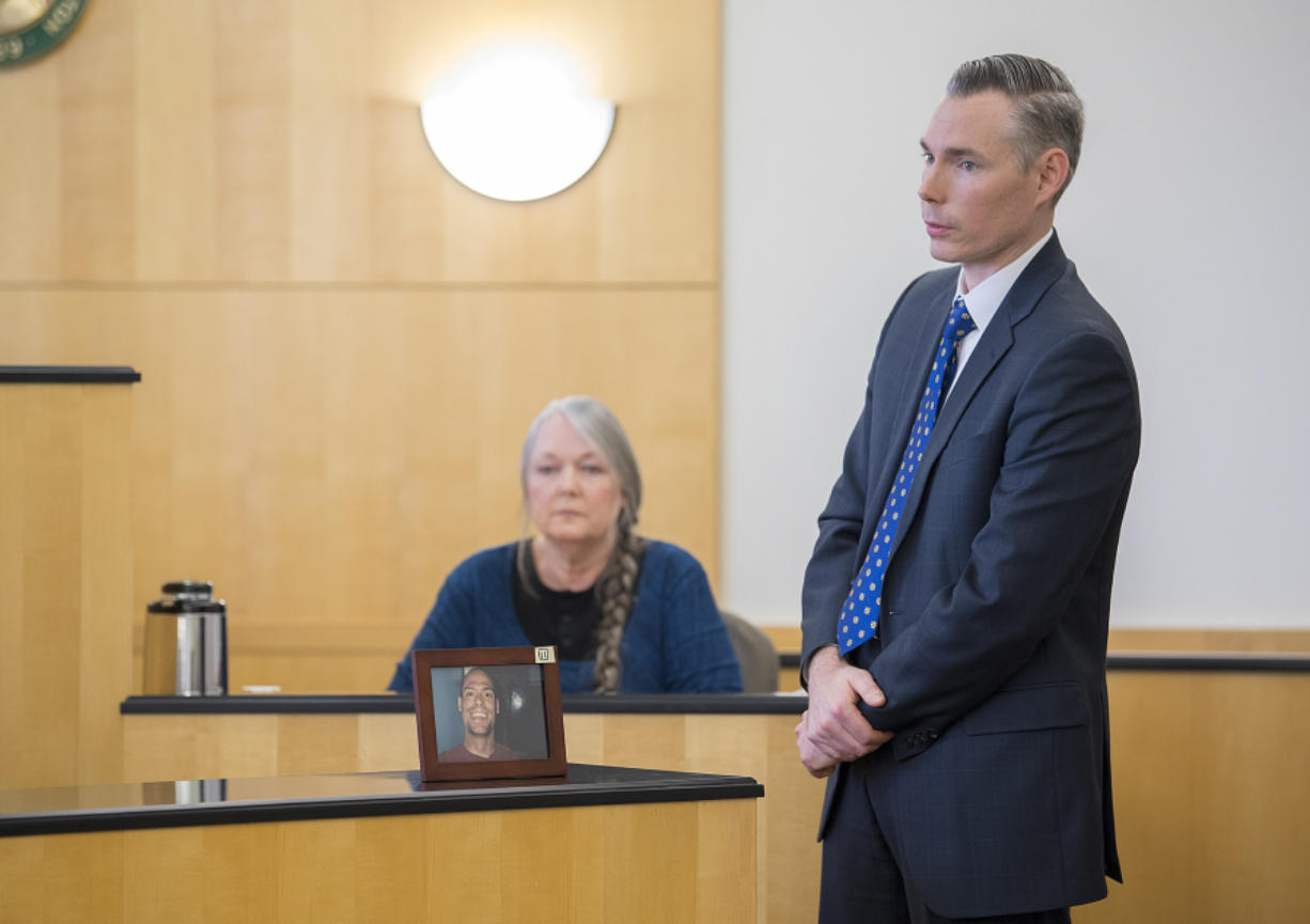 Deputy Prosecutor James Smith, right, speaks to the jury while displaying a framed photo of victim Brandon Maulding as his mother, Linda, background, testifies during Stephen Reichow's murder trial Thursday in Clark County Superior Court. Reichow is accused of beating Maulding to death with a baseball bat in August 2015 in Battle Ground.