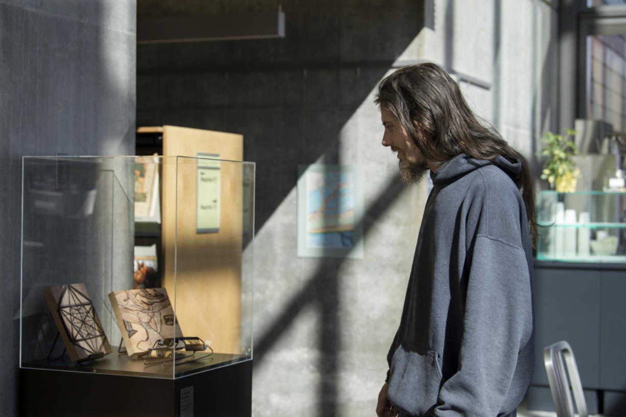 Local artist Jonathon David Turner looks over his wood-burning pictures on display at Vancouver Community Library as part of the Homeless not Hopeless art show.