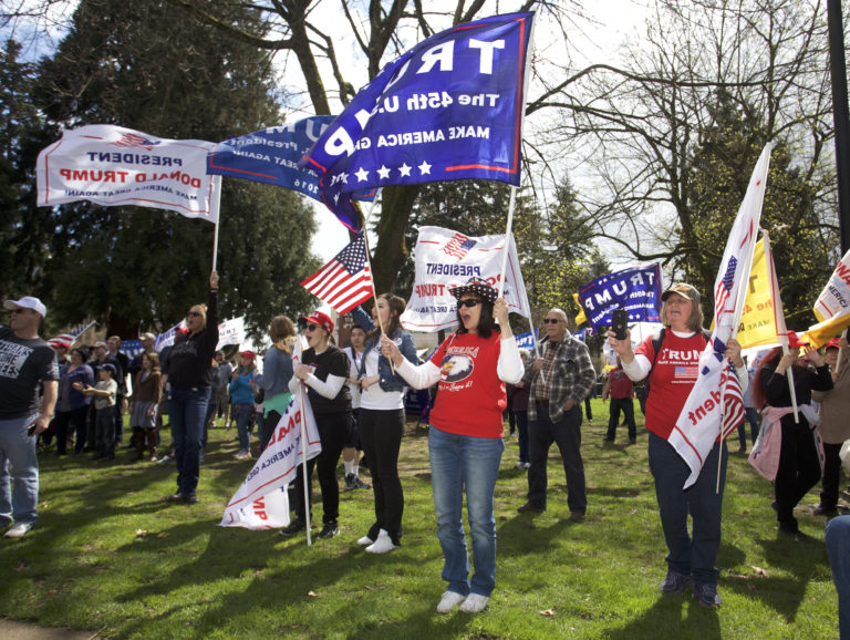 Cathy House of Tacoma, center, waves her flags along with others participating at a rally Sunday in support of President Donald Trump.