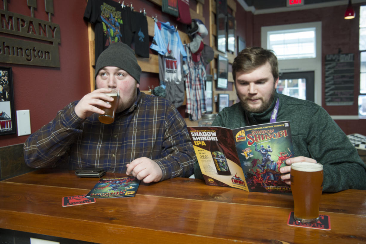 Jake Storgaard, left, takes a sip of the Shadow Shinobi IPA while Sky Cumlander reads the Shadow Shinobi comic book at Loowit Brewing Co. The brewery released the comic book to announce the rebranding of its most popular beer after a copyright dispute.