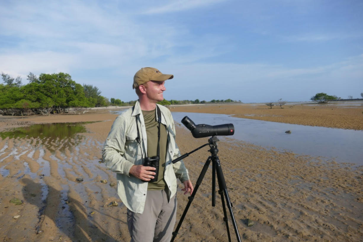 Noah Strycker scans for shorebirds near Denpasar, Bali, in 2015. That year Strycker set a world record for seeing the most birds in a single year. He spoke at an event held by the Vancouver Audubon Society.