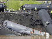 FILE - In this May 1, 2014, file photo survey crews in boats look over tanker cars as workers remove damaged tanker cars along the tracks where several CSX tanker cars carrying crude oil derailed and caught fire along the James River near downtown Lynchburg, Va. Inspectors have found almost 24,000 safety defects over a two-year period along United States railroad routes used to ship volatile crude oil. Data obtained by The Associated Press shows many of the defects were similar to problems blamed in past derailments that caused massive fires or oil spills in Oregon, Virginia and Montana.