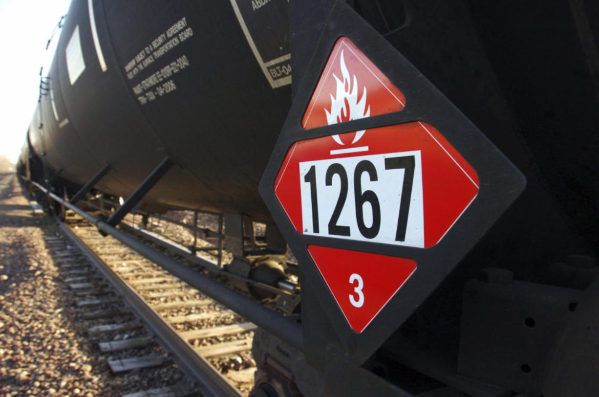FILE - This Nov. 6, 2013 file photo shows a warning placard on a tank car carrying crude oil near a loading terminal in Trenton, N.D. Inspectors have found almost 24,000 safety defects over a two-year period along United States railroad routes used to ship volatile crude oil. Data obtained by The Associated Press shows many of the defects were similar to problems blamed in past derailments that caused massive fires or oil spills in Oregon, Virginia and Montana. (AP Photo/Matthew Brown, File)
