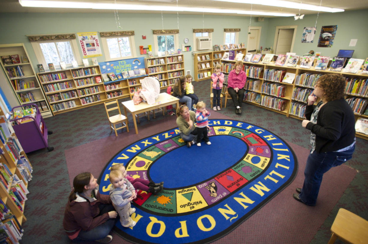 Kids and parents arrive for story time in the Woodland Community Library in 2015. Library advocates say the century-old building is too small, and regional library trustees voted Monday to buy a site for a new branch. Columbian files