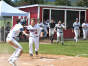 The King's Way Christian baseball team spills out of the dugout after Damon Casetta-Stubbs slides home with the winning run against Cascade Christian.