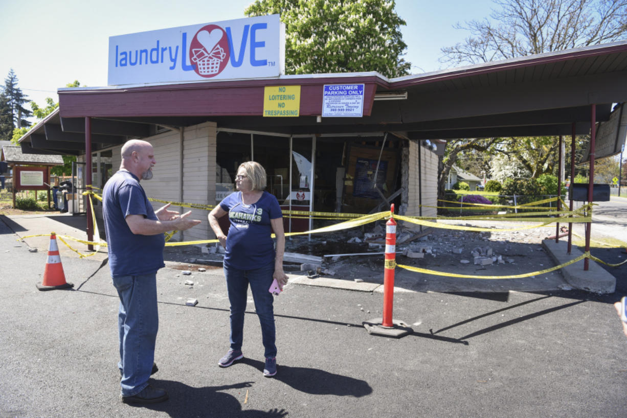 Vancouver resident Kevin Stanfield, left, talks to the manager of Laundry Love, Jackie James, about the damage caused by a Dodge Charger crashing into the front of the building. James heard about the incident soon after it happened.