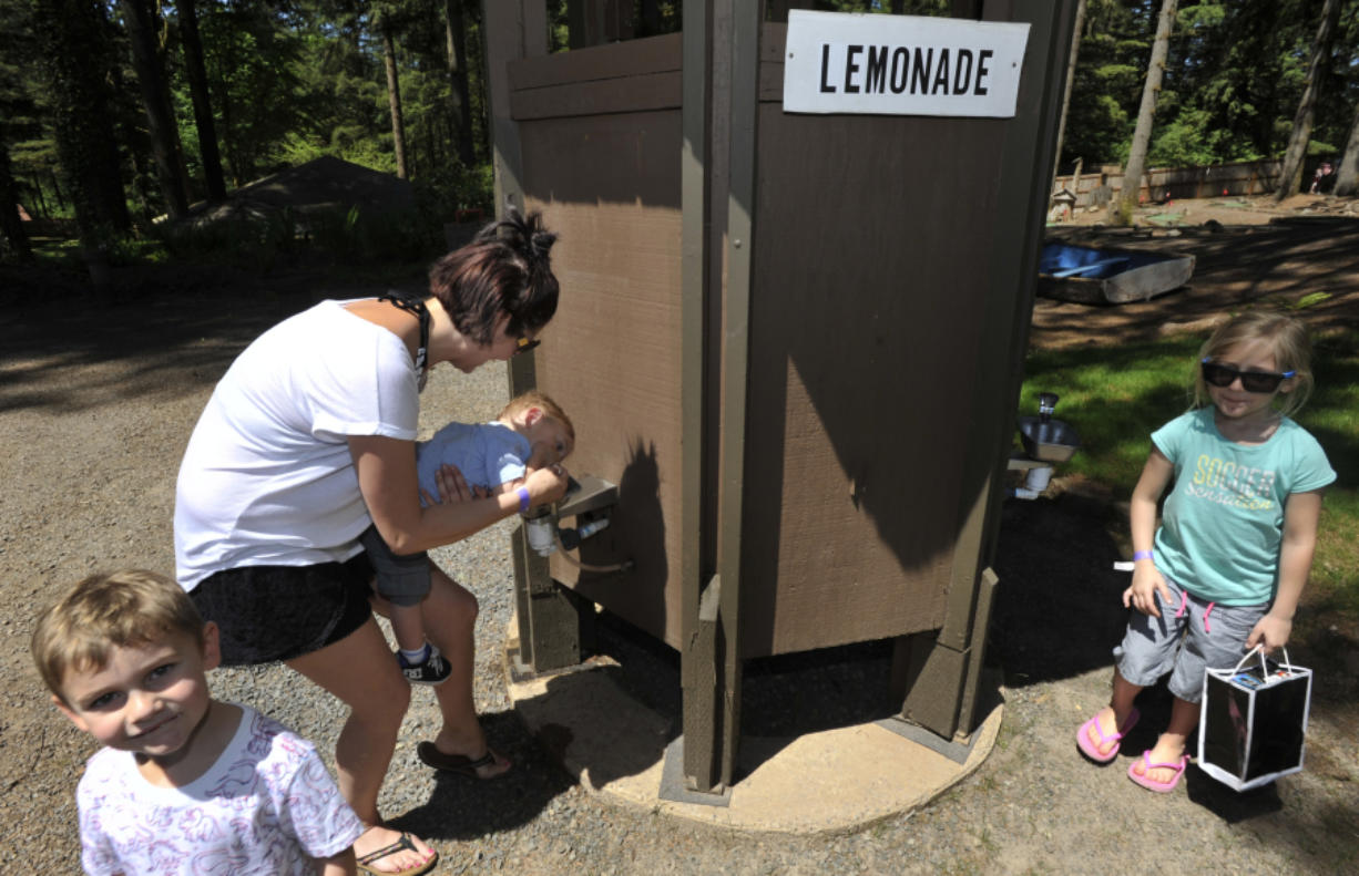 Kolton Groth, left, stands nearby as his brother Cooper, held by Tanya Groth, enjoys some pink lemonade at the fountain at Alderbrook Park in Brush Prairie. The private park, which first opened for events in the 1960s, has been known locally for the lemonade fountains.