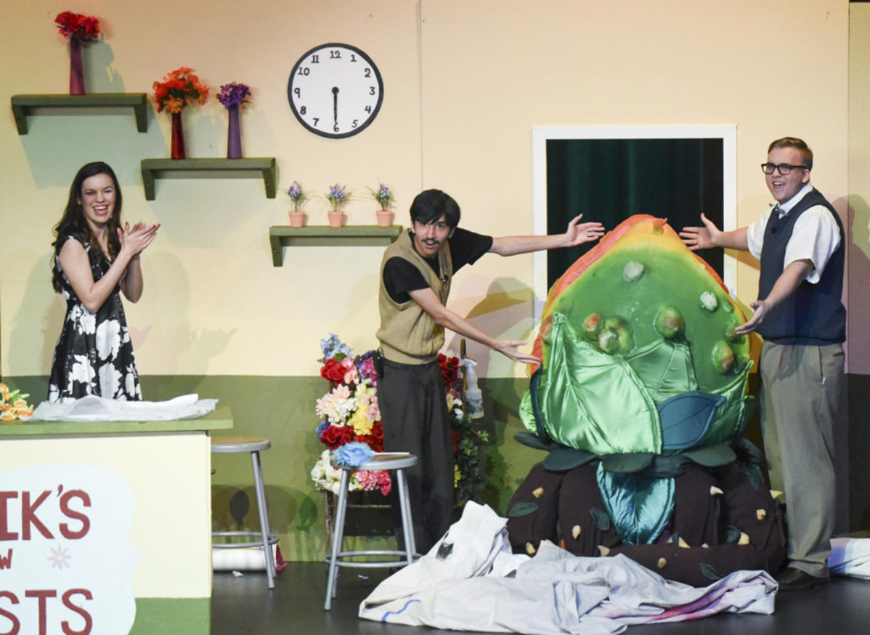 """Woodland High School's """"Little Shop of Horrors"""" will be the school's first musical with live accompaniment in 20 years. Emma Vande Krol, from left, Austin Matthiesen and Mason Hubbard unveil the smaller of two Audrey II puppets, inside which Evelyn Roehn works as the puppeteer. Ariane Kunze/The Columbian"""