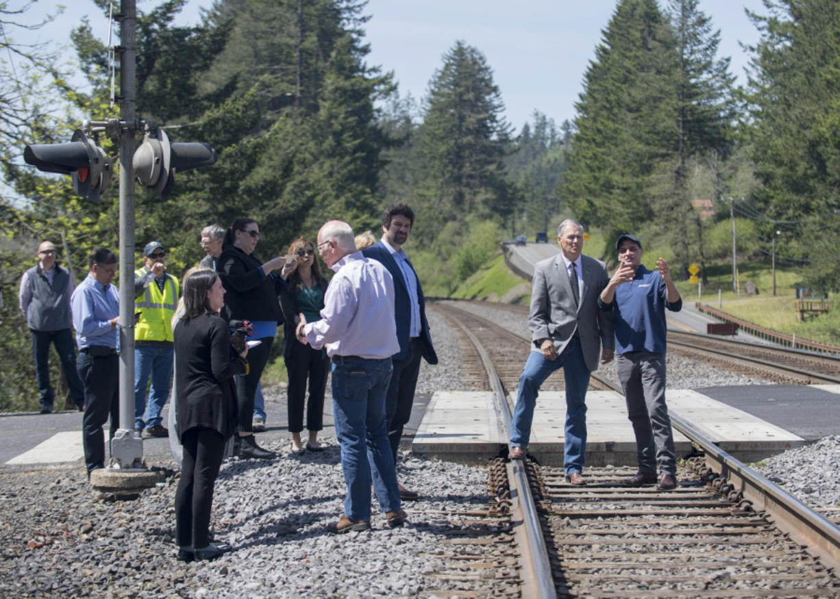Gov. Jay Inslee, second from right, is escorted by BNSF Railway spokesman Gus Melonas as they gather with others Tuesday afternoon at a Skamania County rail crossing to learn more about rail safety.