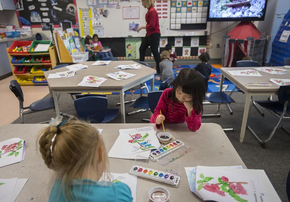 Kindergartner Grace Huynh, 5, facing in pink, joins classmates as they work on a painting during class at Prune Hill Elementary School on April 13.