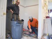 Daniel Culley, right, co-owner of Drytime Restoration, works Thursday with technician Isaac Liss on demolishing a shower that caused water damage to a home in Washougal.