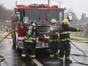 Members of the Vancouver Fire Department clean off after putting out a fire in March.